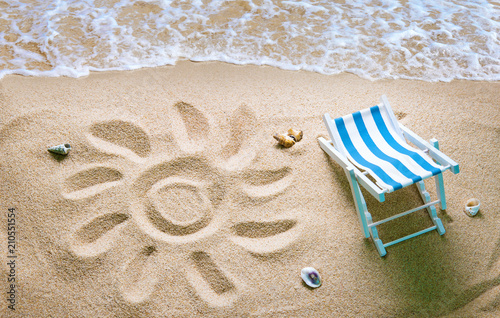 Deckchair on a beach with a sun drawn on the sand - 210551554