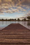 Wooden pier above the lake at the sunrise - 210560103