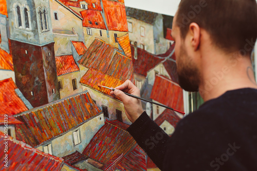 Side back view of man painting houses with colorful roofs  - 210561339