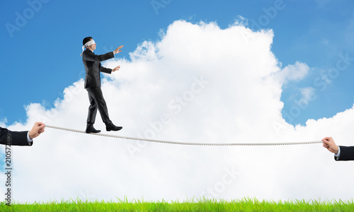 Leinwanddruck Bild Business concept of risk support and assistance with man balancing on rope