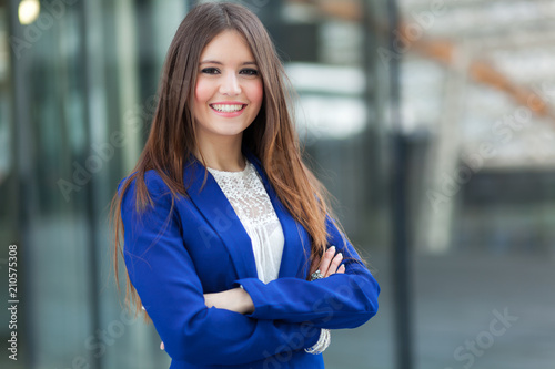 Smiling beautiful businesswoman outdoor in a city setting - 210575308