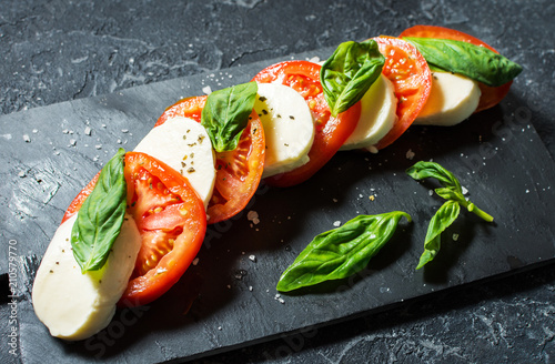 Fototapeta Caprese salad. Mozzarella cheese, tomatoes and basil herb leaves over stone table.