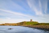 Landscape image of Dunstanburgh Castle on Northumberland coastline in England during late Spring evening - 210580319