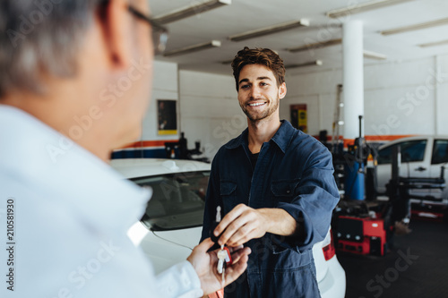 Mechanic giving car keys to customer after servicing