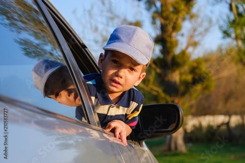 Portrait of cute toddler boy sitting in car. - 210583727