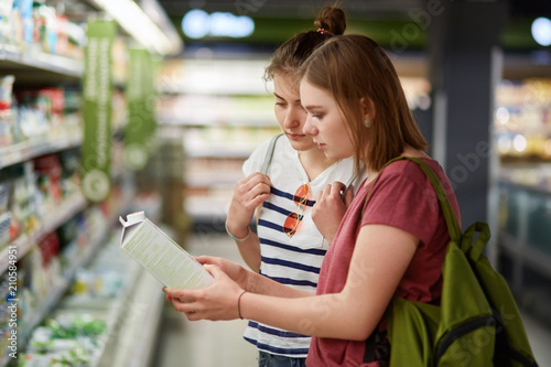37696fb1dea Indoor shot of two young female companions come in store for buying  necessary products, hold