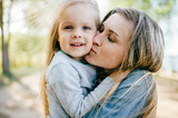 Happy smiling mother hugging her lovely little daughter outdoor. Lifestyle family. Adult cheerful female parent playing with her beautiful emotional child at nature in summer. Positive people faces. - 210597157