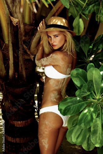 Kobieta w bikini na tropikalnej plaży z palmami