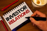 Word writing text Investor Relations. Business concept for Finance Investment Relationship Negotiate Shareholder Hand grasp black marker wooden desk red pen notepad expos texts coffee. - 210606970