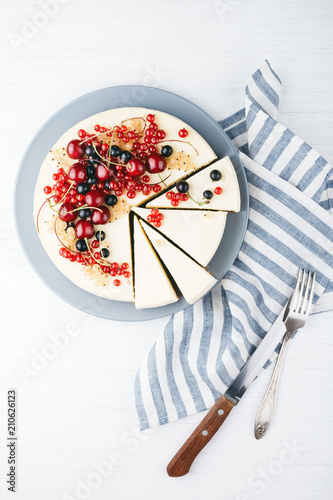 Fototapeta Homemade cheese cake with berries on white wooden table with towel, knife and fork. Top view. Red currant, black currant and cherry.