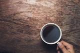 Male hand hold mug of espresso coffee on vintage wood table. - 210627364