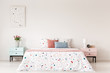 Poster above cabinet with flowers next to bed with colorful pillows in white bedroom interior. Real photo