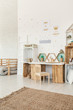 Small wooden chair standing by the desk and crate shelves in white Scandi baby girl room interior with carpet and posters on the wall