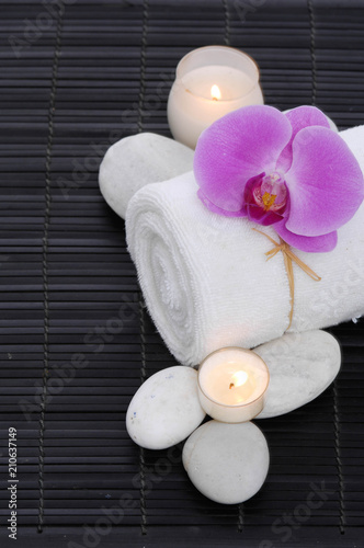Aluminium Spa Spa setting with candle, rolled towel ,orchid, stones on on mat