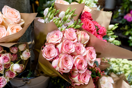 Beautiful bouquets of roses are presented in street flower shop, Italy.