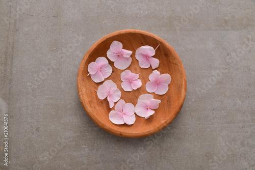 Aluminium Spa Many Pink hydrangea petals in wooden bowl on gray background