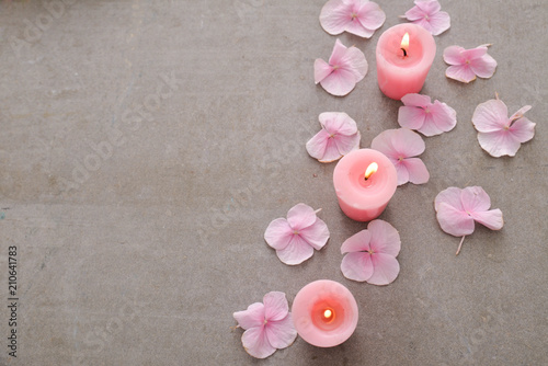 Aluminium Spa Many Pink hydrangea petals with three candle on gray background