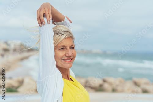 ältere, glückliche frau steht an der küste und streckt entspannt die arme nach oben