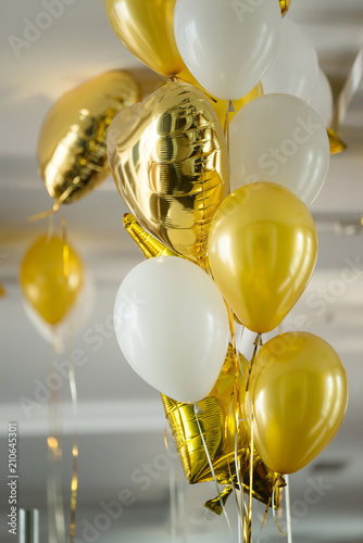 Yellow air balloons and helium gold stars fly