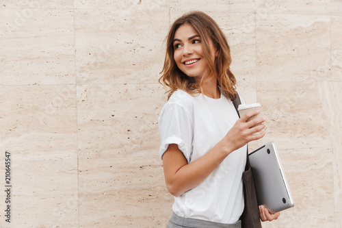 Leinwanddruck Bild Image of joyful european woman walking against beige wall outdoor with silver laptop, and takeaway coffee in hands