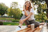 Image of smiling modern woman sitting on bench in green park on summer day, and talking on smartphone with cup of takeaway coffee - 210645731