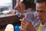Goodbye wife. Close up of attractive male hands holding glass with alcohol and putting ring in it - 210645921