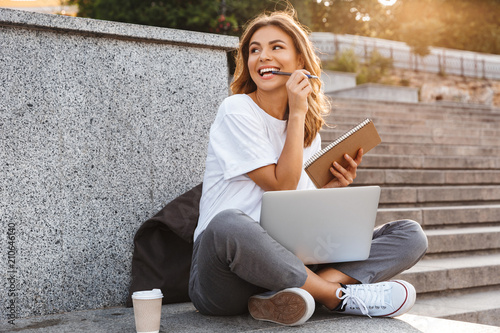 Leinwanddruck Bild Portrait of attractive young woman sitting on city stairs with legs crossed on summer day, and holding notebook with pen while using laptop