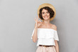 Leinwanddruck Bild - Photo of joyful brunette woman 20s wearing straw hat and summer clothing looking at you and gesturing ok sign with fingers, isolated over gray background