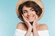 Close up of a smiling young woman in summer hat