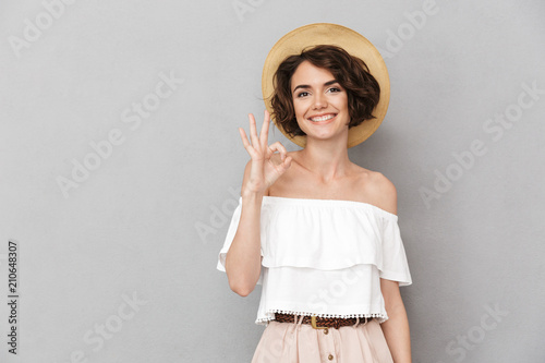 Leinwanddruck Bild Photo of joyful brunette woman 20s wearing straw hat and summer clothing looking at you and gesturing ok sign with fingers, isolated over gray background