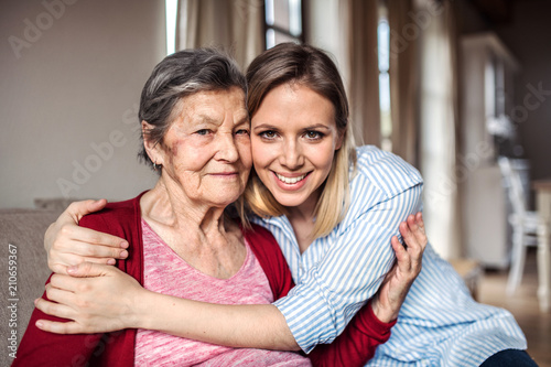 Foto Murales An elderly grandmother with an adult granddaughter at home, hugging.
