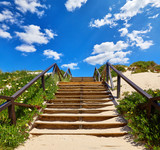 Wooden stairs with railings at the beach buried sand, leading