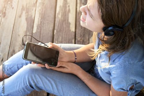 Fotobehang Muziek Teen girl with earphones listening and enjoying music from a smartphone