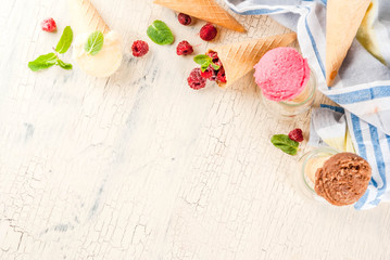 Summer sweet berries and desserts, various of ice cream flavor in cones pink (raspberry), vanilla and chocolate with mint on light concrete background copy space top view