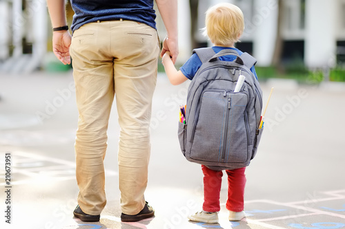 Leinwanddruck Bild Back to school concept. Little pupil with his father. First day of primary school.