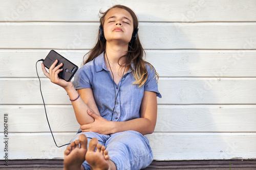 Fotobehang Muziek Teen barefoot girl wearing headphones enjoying music from a smartphone and singing outdoors in summer evening