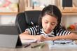 Asian little girl doing homework on wooden table select focus shallow depth of field