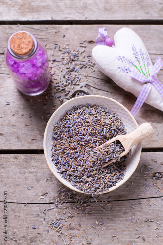 Dry lavender buds bowl, salt with lavender oil and sachet with it on vintage wooden background.