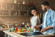Loving african-american couple preparing dinner in loft kitchen