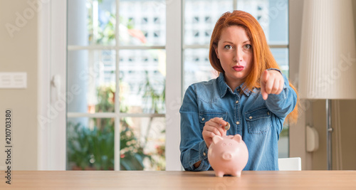 Leinwanddruck Bild Redhead woman saves money in piggy bank at home pointing with finger to the camera and to you, hand sign, positive and confident gesture from the front