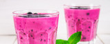 Smoothies of black currant in glass glasses with straws on a white wooden table.