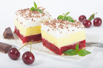 Sweet homemade cherry cake with vanilla and whipping cream on white plate. decorated with chuks of chocolates and mint leaves. Isolated on white background.