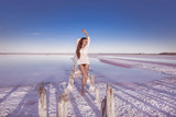 Beautiful free sexy girl in white swimwear posing on salty beach at sunset. Sensual tanned woman with long healthy hair posing on salt pink lake enjoying nature landscape. Luxury summer vacation. - 210712162
