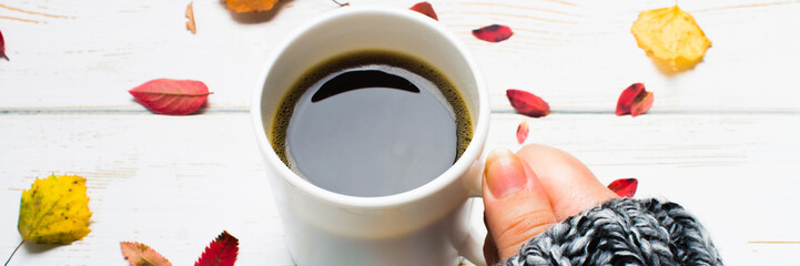 Mug of hot coffee in a woman's hand in a sweater in the autumn setting on a wooden table with a knitted scarf, sweater. Comfort, warmth, cozy. banner © detry26
