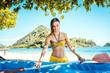 Woman in bikini with a kayak on an island in front of beach