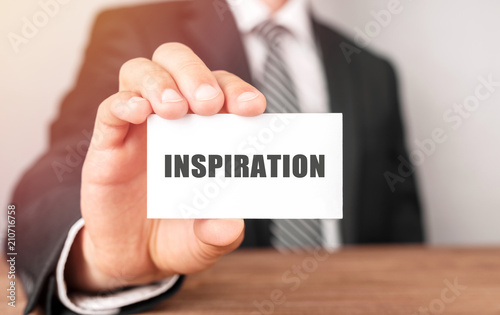 Businessman holding a card with text Inspiration
