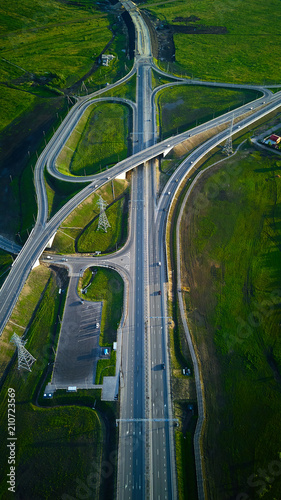 Aerial view of highway junction and overpass in city on a sunset hours. Vertical image.