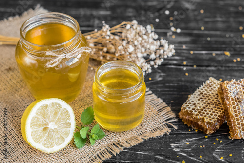 Fototapeta Beautiful transparent honey in bank, honeycombs and pollen on a wooden table. It can be used as a background