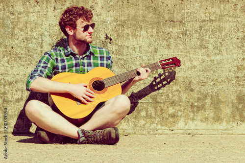 Young bearded hipster man with guitar outdoor - 210739350