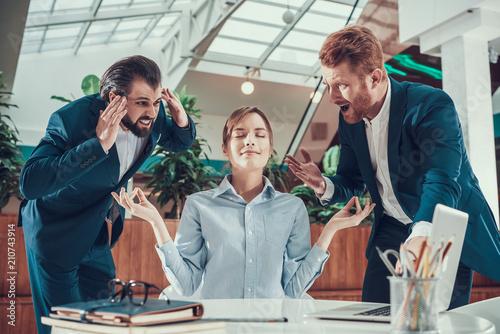 Leinwanddruck Bild People shout at meditating worker in office.